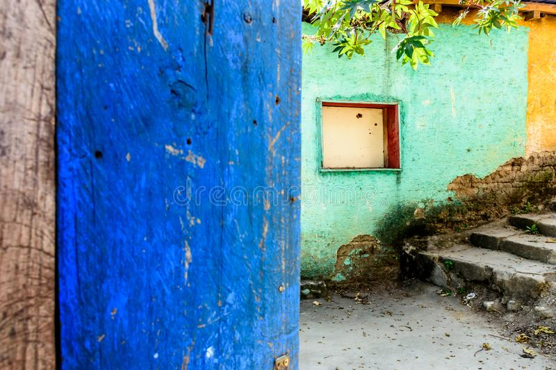 Rustic open blue door & turquoise & yellow wall. Rustic open blue painted door & turquoise & yellow building wall with boarded up window in Guatemala, Central stock image