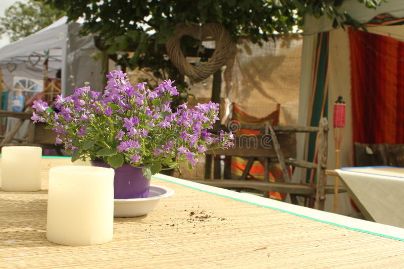Rustic outdoor relaxation. Relaxing outdoors on wooden benches for a festival with pretty flowers and candles on the table and tent stalls in the background stock photo
