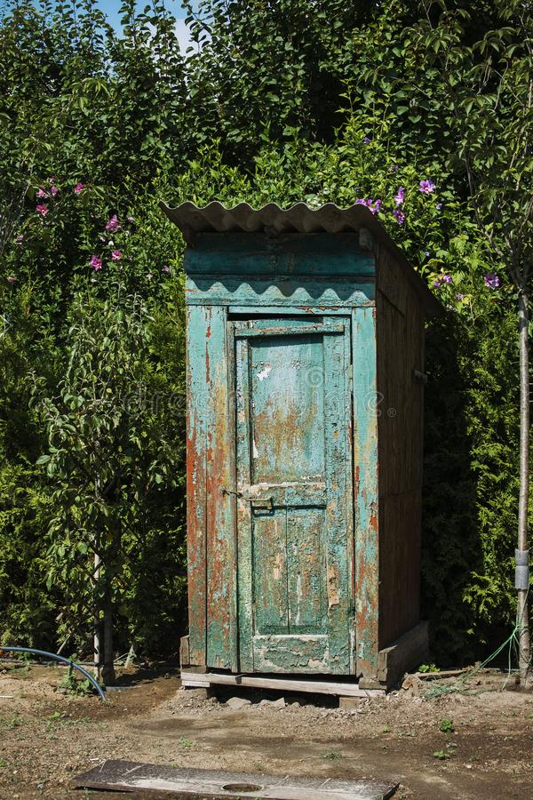 Rustic outdoor toilet stands in the garden. Sparkling, reflecting the sunshine light stock images