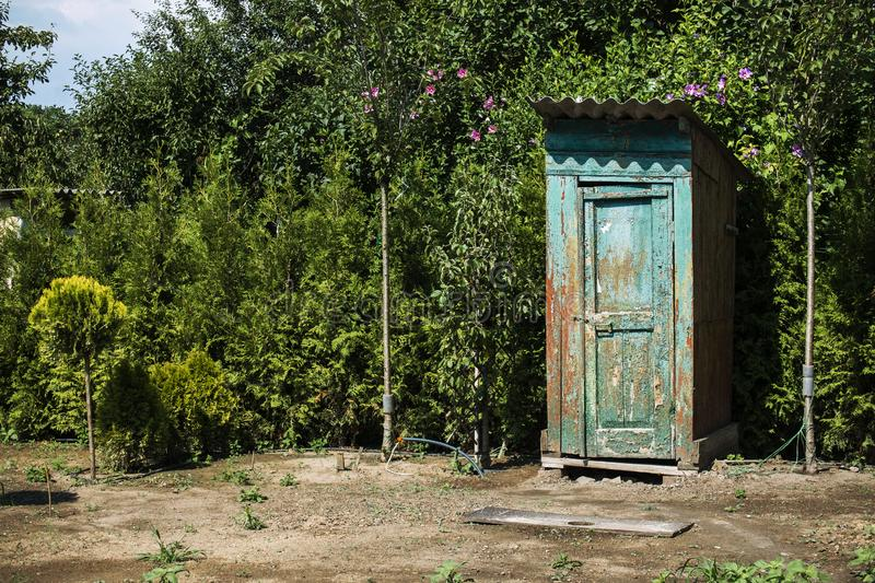 Rustic outdoor toilet stands in the garden. Sparkling, reflecting the sunshine light stock photography