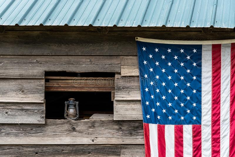 Rustic outside wall of wood building with green metal roof, open window with dusty lantern on windowsill, American flag hanging on stock photos