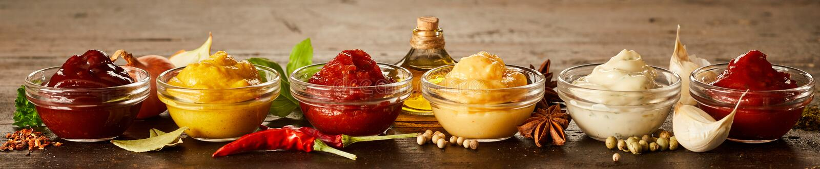 Rustic panorama banner with homemade sauces. Rustic panorama banner with a variety of individual homemade sauces and marinades in glass bowls with fresh herbs royalty free stock photo