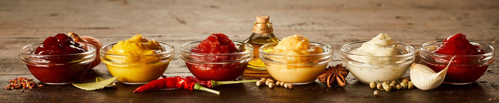 Rustic panorama banner with sauces and marinades. Rustic panorama banner with assorted small glass bowls of sauces and marinades together with spices and royalty free stock images