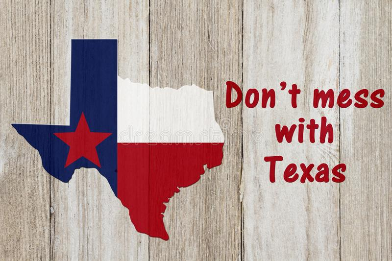 A rustic patriotic Texas message. Map of Texas with the Texas Flag colors on weathered wood background with text Don `t mess with Texas royalty free illustration