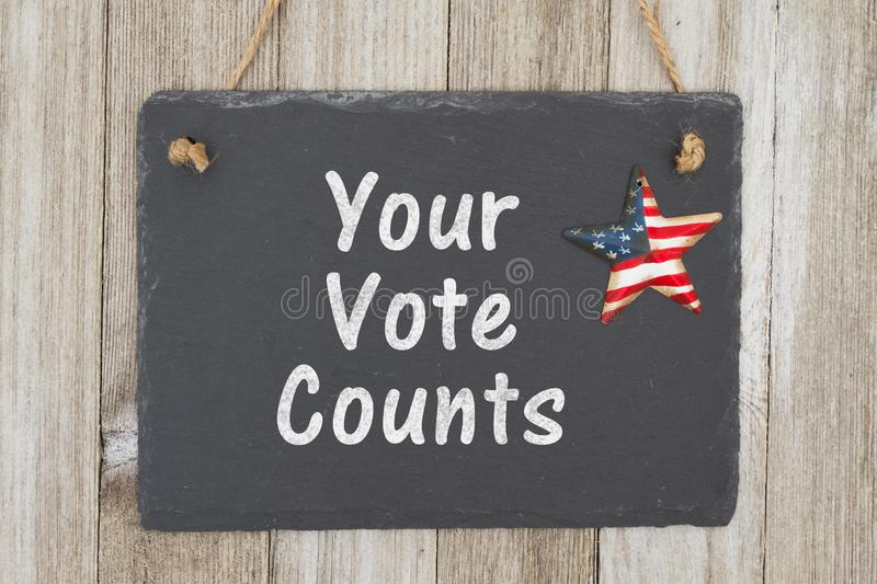 A rustic patriotic voting message. A retro chalkboard with a vintage USA star hanging on weathered wood background with text Your Vote Counts stock images