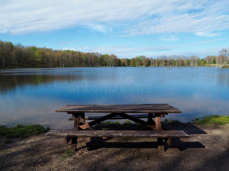 Rustic picnic table next to mountain lake royalty free stock images