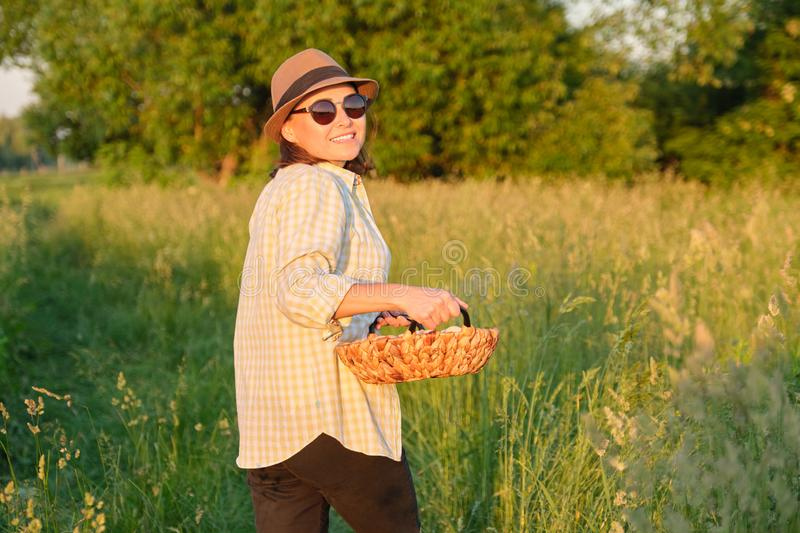 Rustic portrait of mature woman with basket of eggs at meadow, golden hour stock images