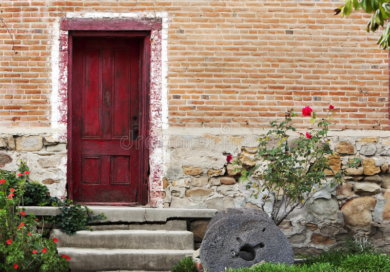 Rustic Red Door Brick Stone Building. An old crumbling brick and stone building with a weathered red door, concrete steps leading to door, old stone wheel near royalty free stock photo