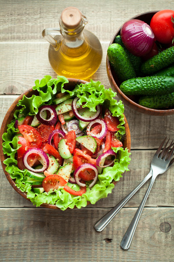 Rustic salad of fresh tomatoes, cucumbers, red onions and lettuce, dressed with olive oil and ground pepper in a wooden bowl. Top. View royalty free stock photo