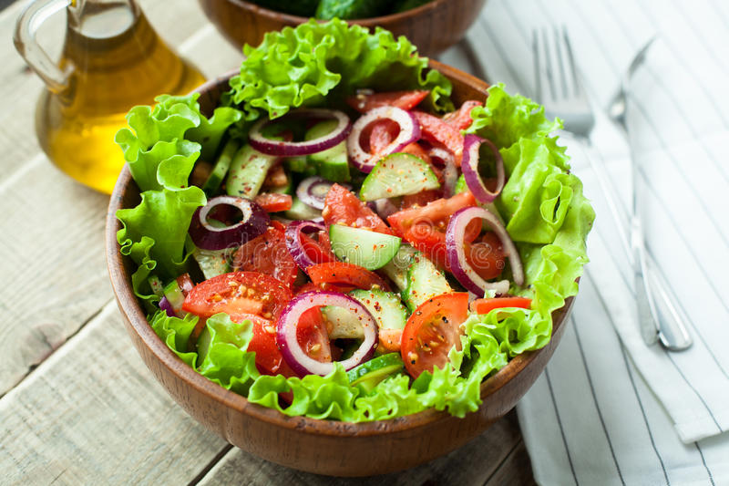 Rustic salad of fresh tomatoes, cucumbers, red onions and lettuce, dressed with olive oil and ground pepper in a wooden bowl. Top. View royalty free stock images