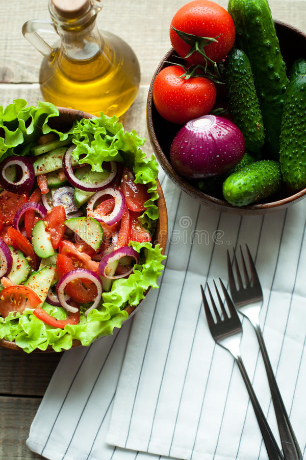 Rustic salad of fresh tomatoes, cucumbers, red onions and lettuce, dressed with olive oil and ground pepper in a wooden bowl. Top. View stock photography