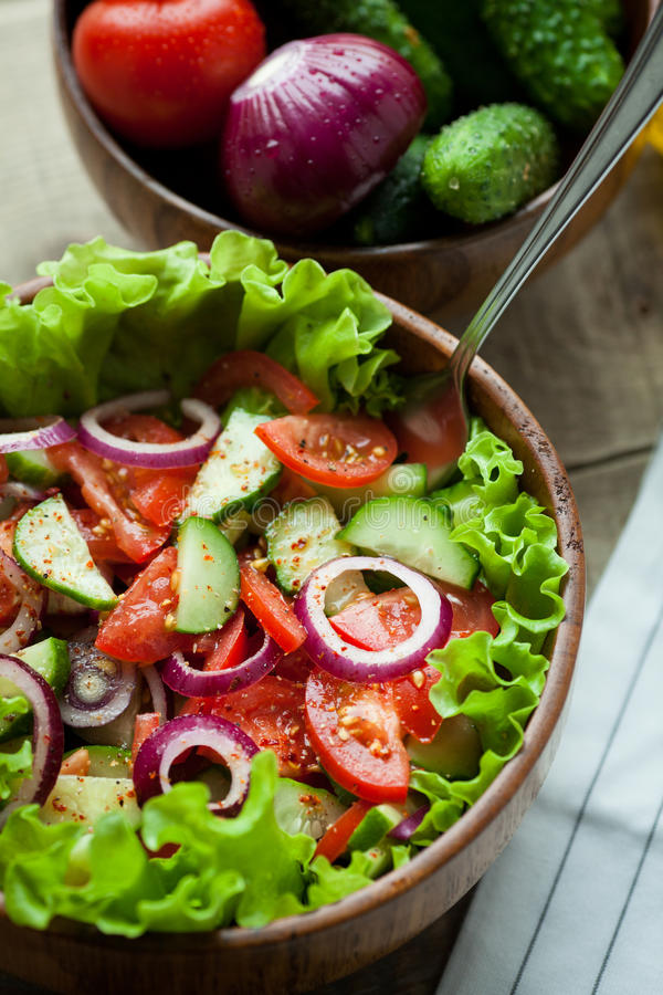 Rustic salad of fresh tomatoes, cucumbers, red onions and lettuce, dressed with olive oil and ground pepper in a wooden bowl. Top. View stock photo
