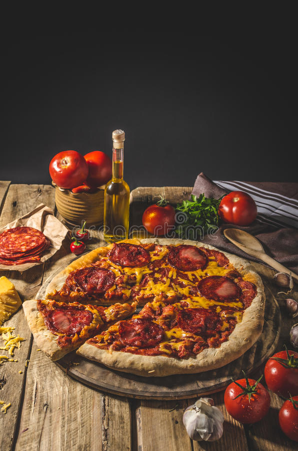 Rustic salami pizza with cheddar cheese and chorizo royalty free stock photos