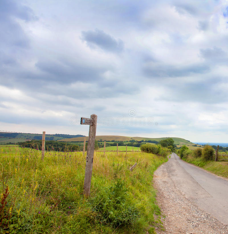 Rustic signpost pointing to Ditchling Beacon. A wooden rustic signpost pointing toward the Ditchling Beacon on a country road in the beautiful South Downs in royalty free stock image