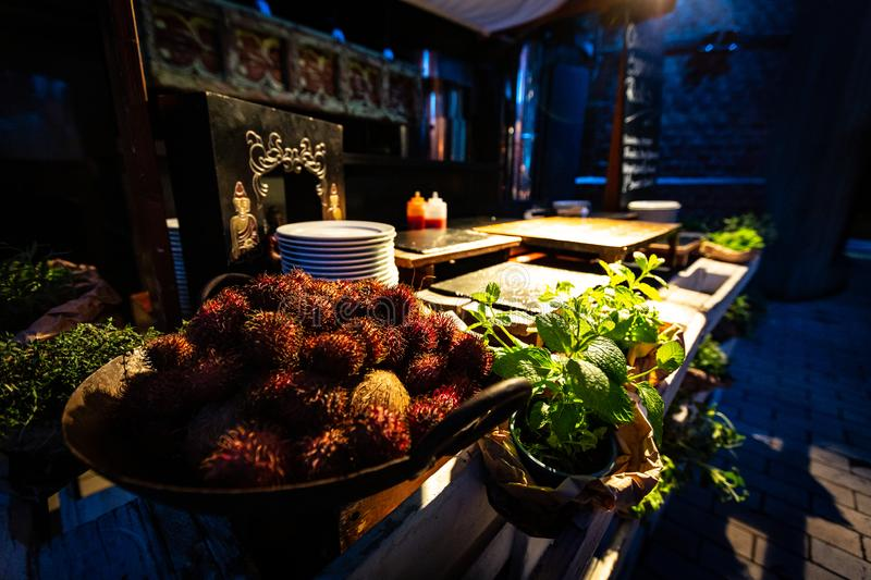 Rustic South East Asian style Street Food Stand. An exotic south East Asian street food stand in restaurant with lychees and fresh herbs, ambient lighting stock photography