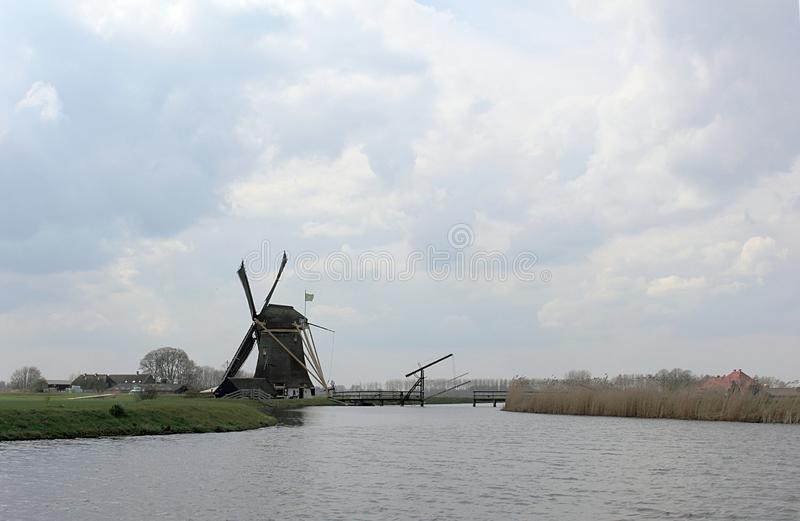 Rustic spring landscape with dutch windmill. Near the water canal royalty free stock image