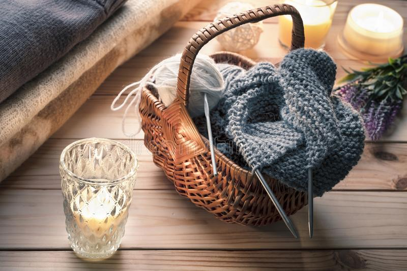 Rustic still life with knitting yarn, needles, wicker basket. Wooden table, candles. royalty free stock image