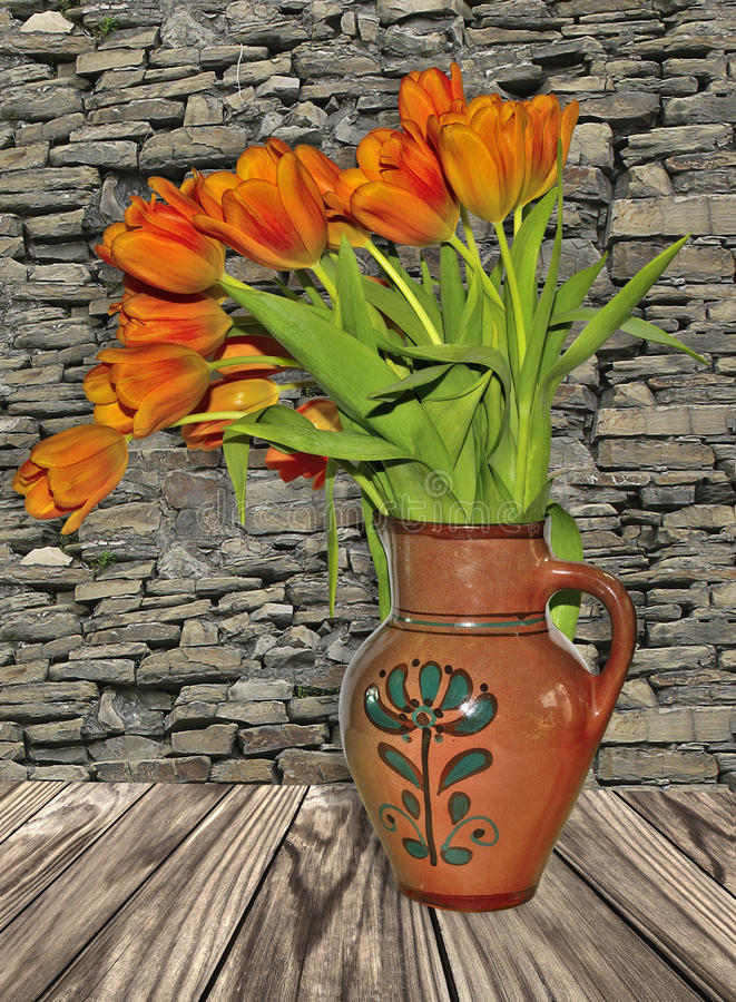 Rustic stillife with red tulips in old clay jug. On the wooden surface. Texture of background - ancient stone wall stock photos