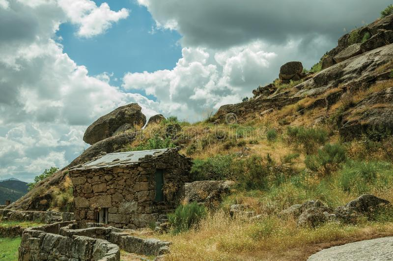 Rustic stone house on a hilly landscape. With rocks and bushes, in a cloudy day near Loriga. Known as the Portuguese Switzerland for its landscape at Serra da stock image