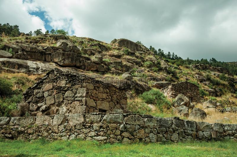 Rustic stone house on a hilly landscape. Rustic stone house and wall on hilly landscape with rocks and bushes, in cloudy day near Loriga. Known as the Portuguese royalty free stock photo