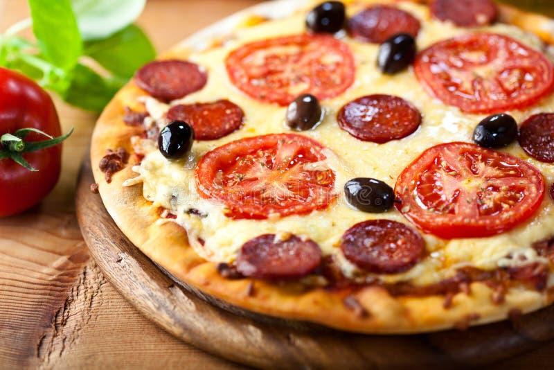 Rustic stonebaked pizza with chorizo salami royalty free stock photography