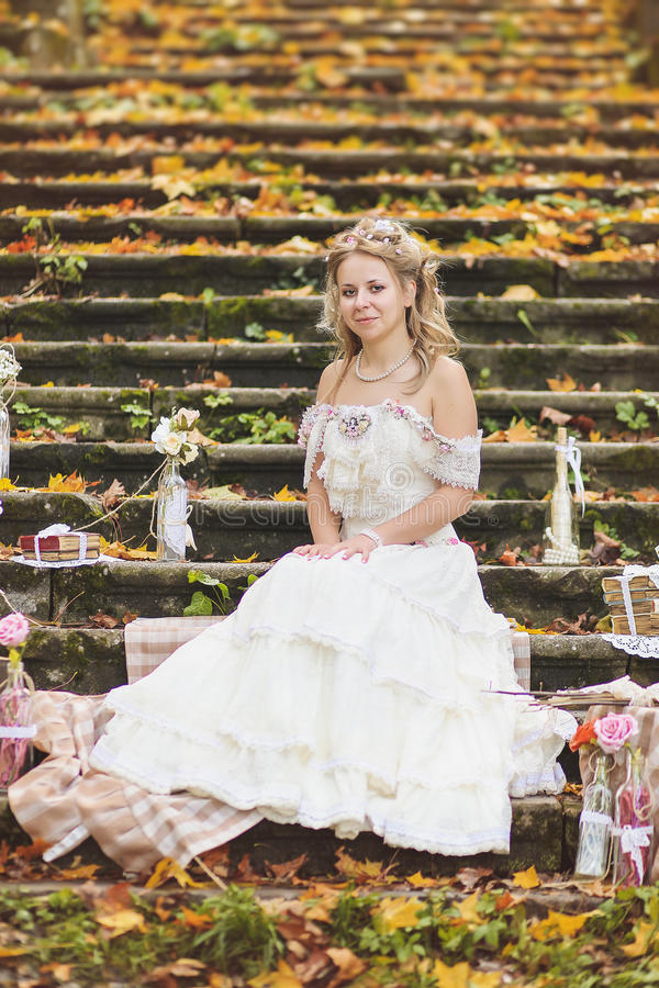 Rustic style bride sitting on stone steps at sunny autumn forest, surrounded by wedding decor. stock images
