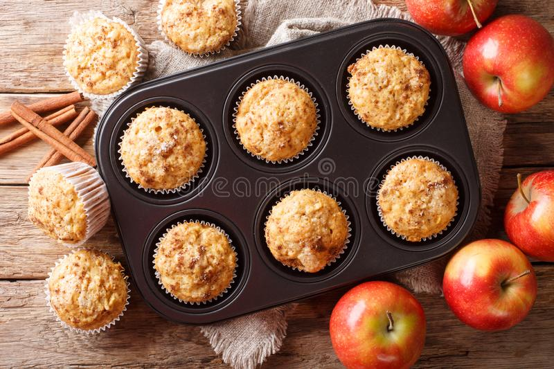 Rustic style fresh apple muffins with cinnamon close-up on the table. Horizontal top view. Rustic style fresh apple muffins with cinnamon close-up in a baking royalty free stock images