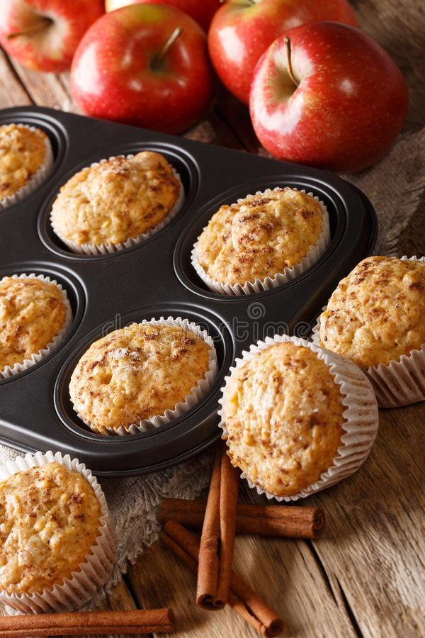 Rustic style fresh apple muffins with cinnamon close-up on the table. vertical. Rustic style fresh apple muffins with cinnamon close-up in a baking dish on the stock photos
