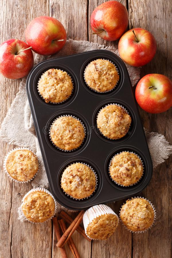 Rustic style fresh apple muffins with cinnamon close-up on the table. Vertical top view. Rustic style fresh apple muffins with cinnamon close-up in a baking dish stock photo