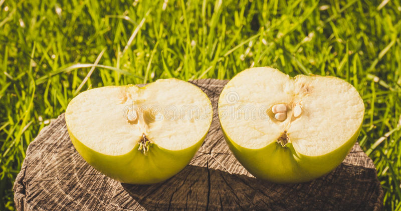 The rustic style. Half green Apple on the background of an old wood. Green fresh Apple cut into two equal halves on the background of old dry wood and green lawn stock photo