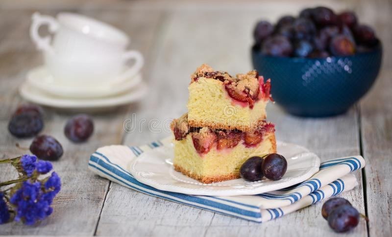 Rustic style. Homemade plum cake on wooden table stock image