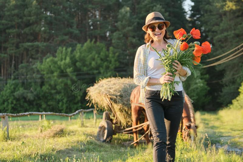 Rustic style, mature happy woman in hat with bouquets of poppies flowers walking along country road royalty free stock images