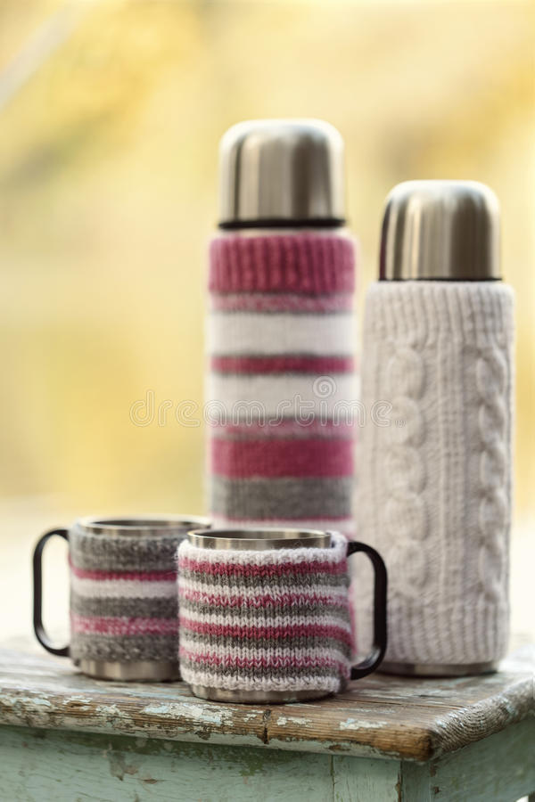 Rustic style. On the old stool is a thermos with cups in knitted. Covers royalty free stock images