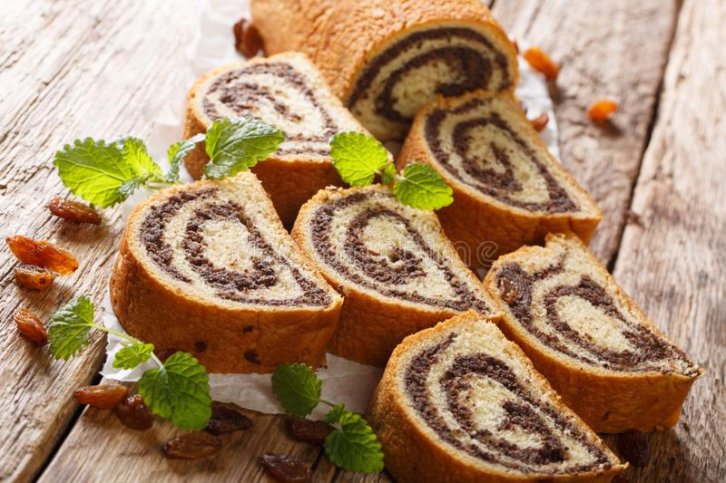 Rustic style poppy roll with raisins, nuts decorated with mint close-up on parchment on a wooden table. horizontal royalty free stock image