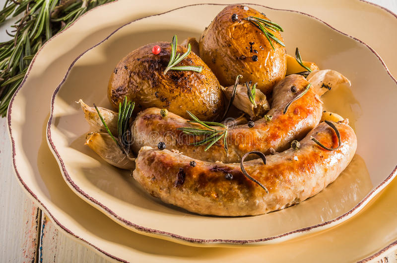 Rustic style potatoes and fried sausages. With rosemary, garlic on a wooden white background royalty free stock photography