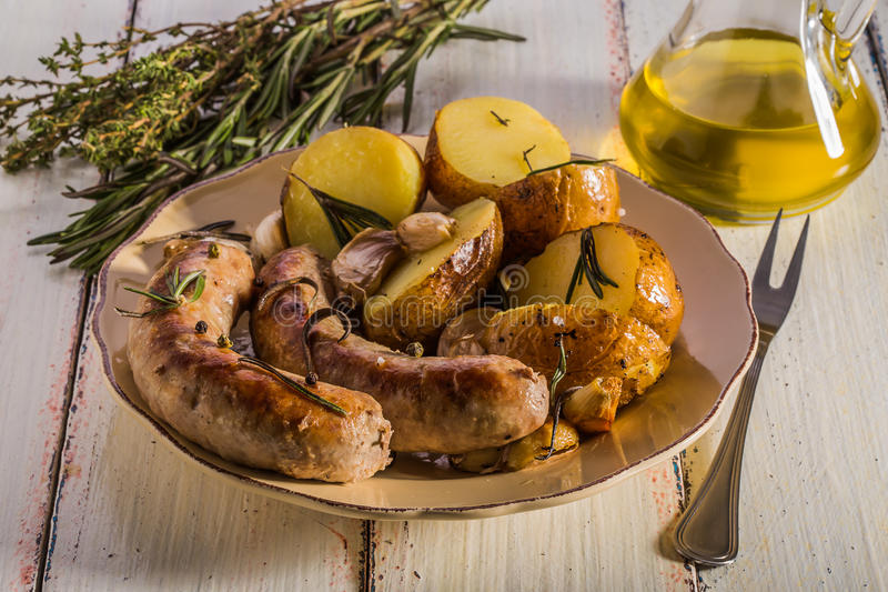 Rustic style potatoes and fried sausages. With rosemary, garlic on a wooden white background royalty free stock photos