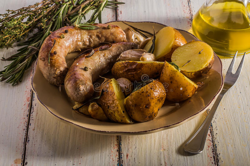 Rustic style potatoes and fried sausages. With rosemary, garlic on a wooden white background stock photo