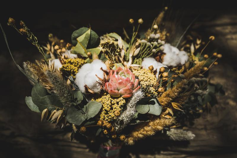 Rustic style wedding bouquet with dried flowers. Wedding bouquet with dried flowers. Cotton, succulent, spikelets of wheat and other. Dark background stock photo