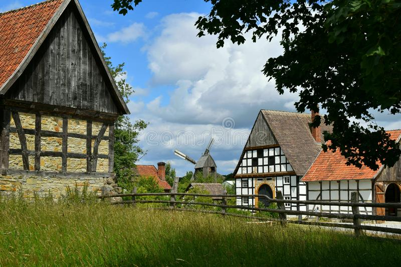 Rustic summer landscape. Beautiful village photo, old houses, green grass, blue sky. German picturesque old houses on a background of green forest. Germany royalty free stock image