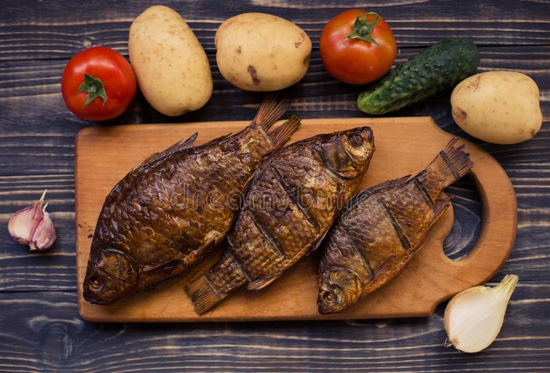 Rustic table with food. Food, on a wooden table. Fried fish, deliciously cooked, picnic. royalty free stock photos