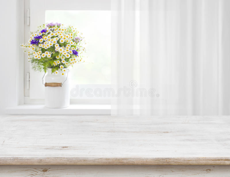 Rustic table in front of wild flowers on wooden window stock image
