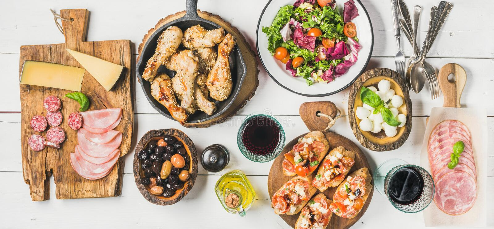 Rustic table set with chicken, salad, different snacks and wine. Home dinner table arrangement. Rustic table set with salad, olives, chicken, brushettas royalty free stock images