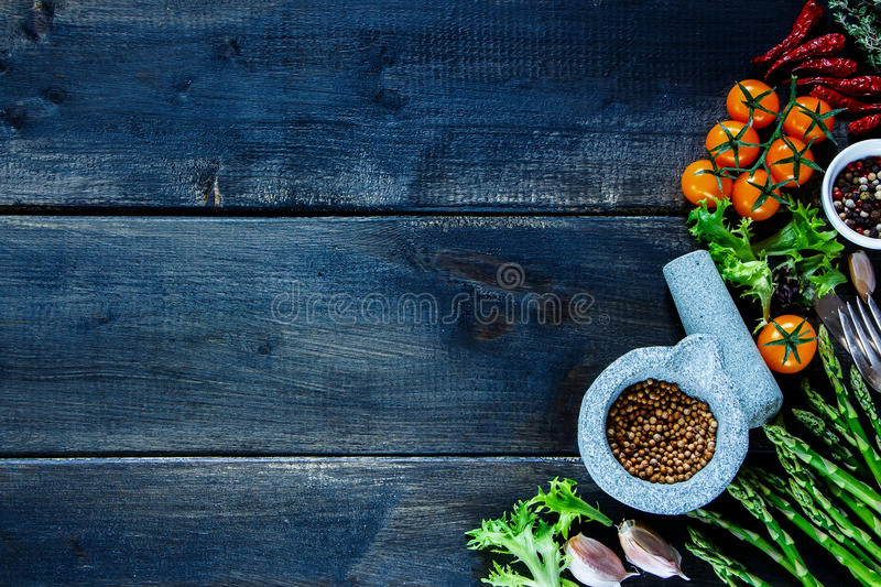 Rustic table with various colorful spices and vegetables royalty free stock images