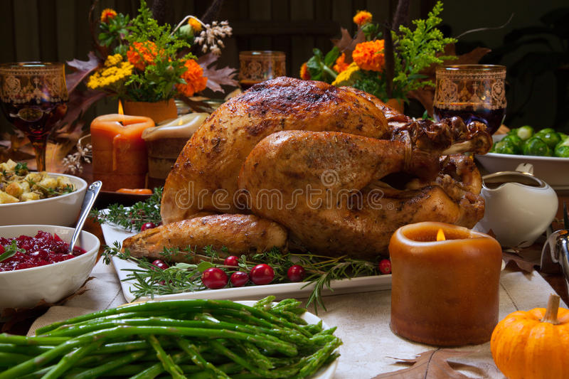 Rustic Thankgiving Dinner. Roasted turkey garnished with cranberries on a rustic style table decoraded with pumpkins, gourds, asparagus, brussel sprouts, baked royalty free stock images