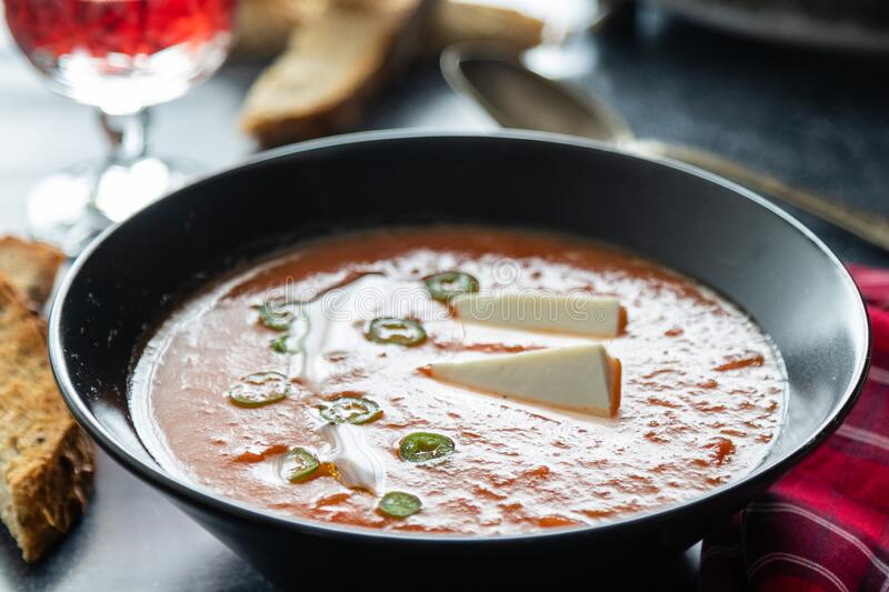 Tomato soup with white cheese in black bowl royalty free stock photo