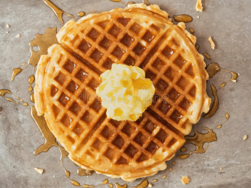 Rustic traditional waffle with butter and maple syrup. Close up of rustic traditional waffle with butter and maple syrup royalty free stock photo