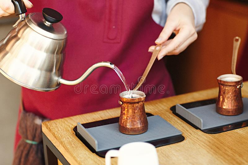 Rustic Turkish cezve, coffeepot, ibrik with boiled coffee beans, water, spices, cinnamon, salt on electric stove and wooden table. stock photography