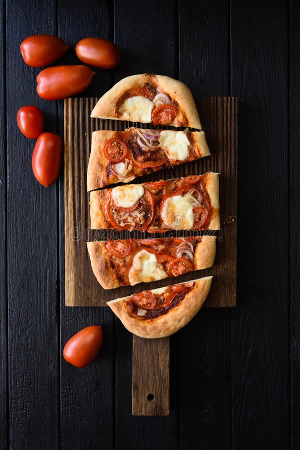 Rustic vegetarian pizza. Freshly baked oval pizza with vegetables served with raw tomatoes on black background top view royalty free stock image