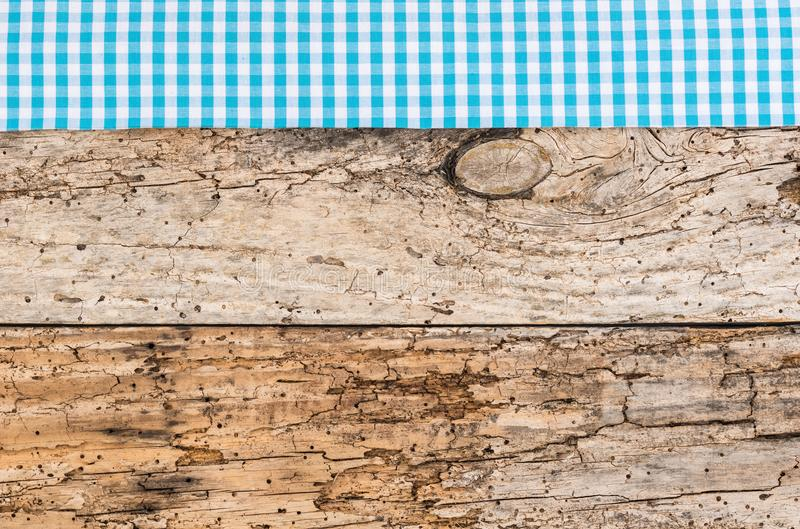 Oktoberfest background old wood with bavarian rustic blue checked tablecloth border. Rustic vintage wooden table surface with blue checkered cloth, top view stock image