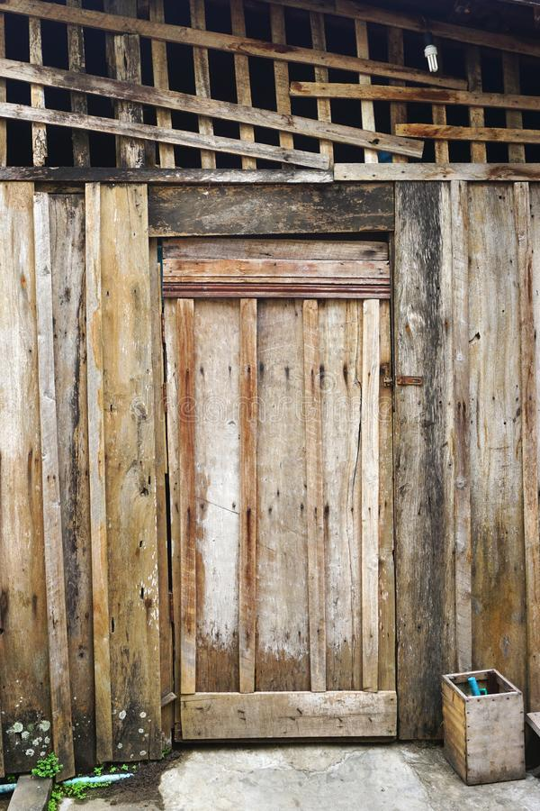 Rustic weathered wooden entry door in rural Laos. Funky wooden building with rustic lattice above the entry door in rural Laos. Walls and door use board and royalty free stock image